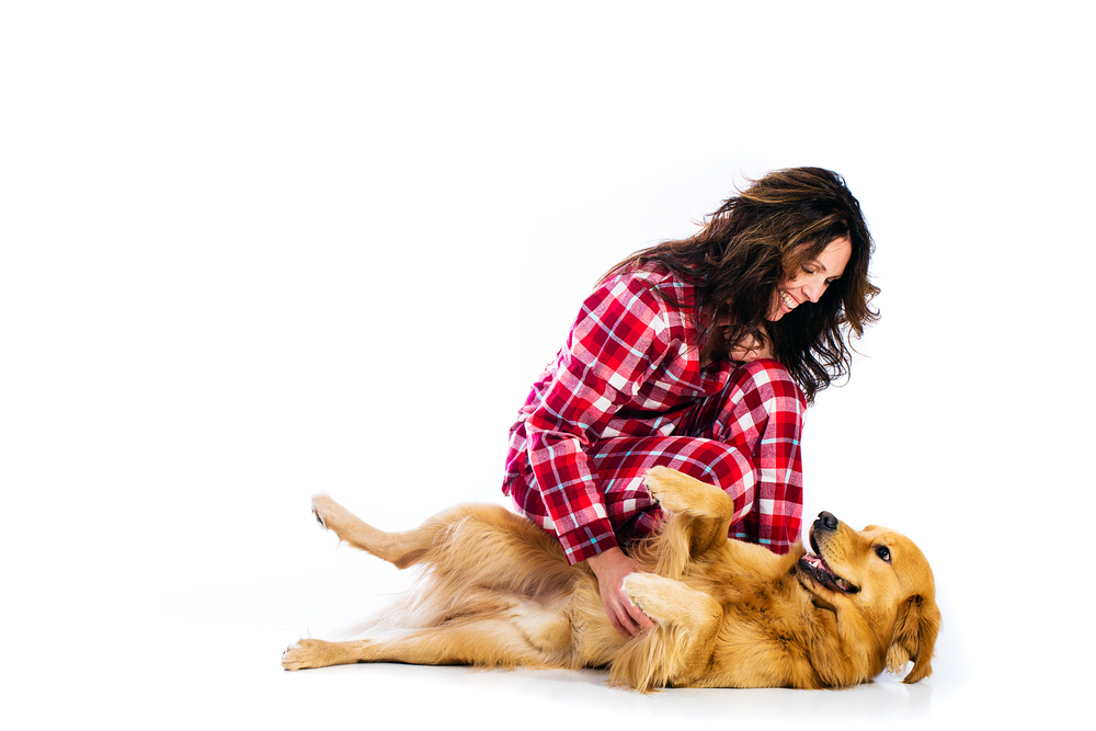 Woman scratching dog's belly